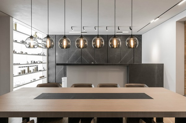 The second home design is another Moscow based property, created by Mezhevova Dean, which covers an overall area of 311 square meters. Here, a smoky natural stone finish on the kitchen cabinetry works beautifully behind a row of seven twinkling lights suspended over a long dining table.