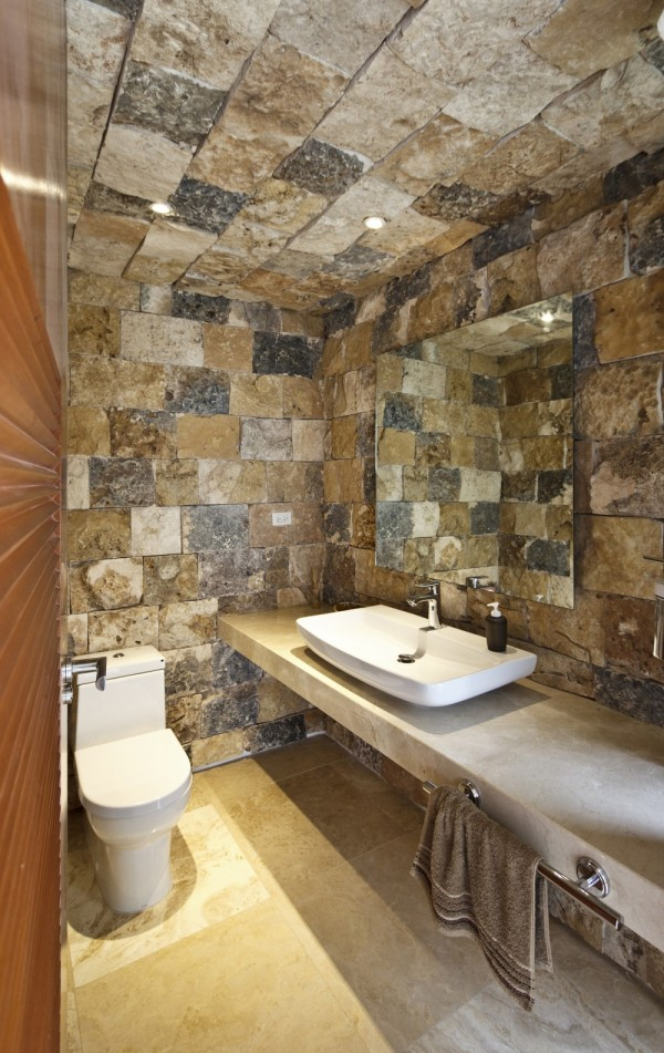 The same stone wall design we see outside of the building becomes the decoration in this bathroom suite.