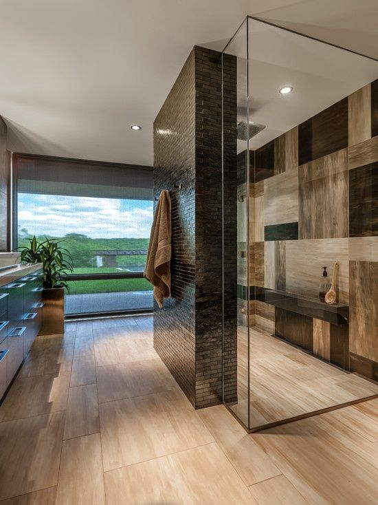 A stunning irregular checkerboard effect has been achieved in this shower enclosure by teaming different shades and cuts of the same tile material together. An extruded shelf fits perfectly with the look.