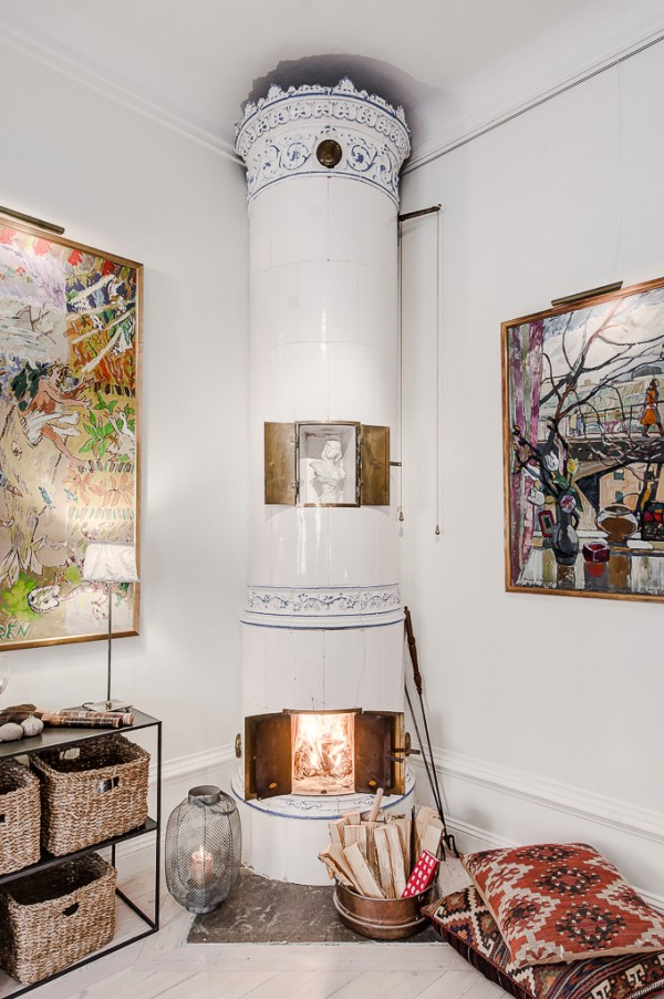 Over in one corner, a ceramic wood burning stove, of an antique Scandinavian design, creates an elegant statement in a blue and white palette that would look equally at home in a Greek interior.