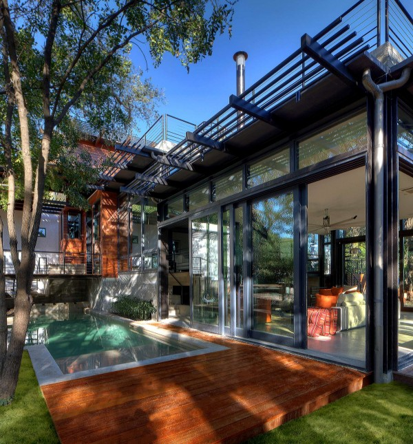 The airy open layout of the interior connects with its exterior surroundings via huge windows and retractable glass doors. It is through these such doors that the living room sweeps out onto the decking that surrounds the swimming pool, the established gardens and outdoor entertaining areas.