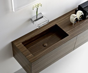 This block walnut vanity unit with integrated basin keeps a contemporary scheme looking streamlined. The wall mounted faucet takes the form of a neat glass shelf, complete with a place for a small floral display.