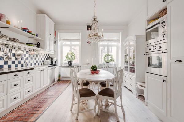 The kitchen design expands on the blue and white colorway, where a long backsplash has been created from a checkerboard of tiles. The kitchen units themselves are of a traditional white wooden design with shell cup handles, opposite a more ornate dresser and a white painted dining set. The furniture selection creates a homey french farmhouse look, which has been complimented with the introduction of warm toned terracotta floor tiles, against white washed floorboards.