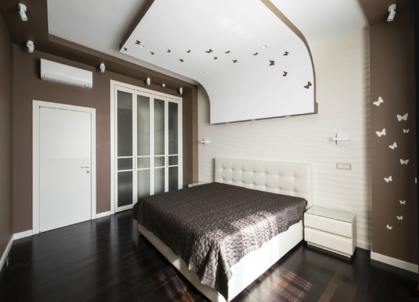 In the taupe bedroom, a curvaceous ceiling structure has been installed as a fun alternative to an oversized headboard. Butterfly cutouts decorate the unusual installation, and a nearby wall displays the negative colorway of the pretty effect.