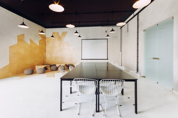 In the work area, a large conference table is formed out of many smaller tables that can be broken apart to allow multiple working formations, including individual desks if the need arises.