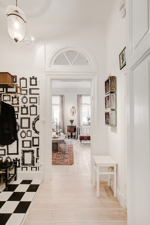 Striking black and white décor adorns the hallway, including a quirky picture frame wallpaper print. More checkerboard tiling covers the floor area beneath a coat rack and shoe stand-a sensible choice for keeping mud and rainwater drips from warping the otherwise wooden flooring.