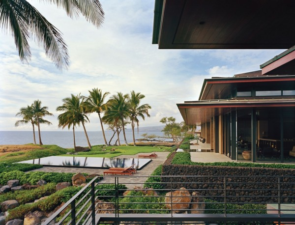 Raised up on a picturesque promontory of volcanic rock, the exterior of this tropical home is a strong contemporary vision, with broad overhangs to shade the interior quarters from the blazing Hawaiian sunshine. An infinity pool stretches out alongside a selection of mature palm trees, surrounded by a stone sun deck.
