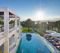 Beyond the holiday home's large gardens with mature palm trees and shrubs, the glorious view continues all the way out to the sea. A bank of sun loungers are set to soak up the suns rays on a deck that runs alongside a generous infinity pool.