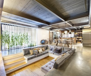 The interior embraces a loft feel with exposed brick faces, rustic ceiling beams, industrial ducting, and concrete floors. However, the stark backdrop almost fades away with the introduction of warming woods and plush furniture, amongst the homes pretty landscaped heart.