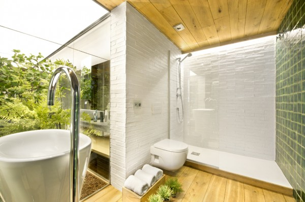 One of the few privately walled areas of the home is the bathroom, though the wash basin here still benefits from an indoor garden view.