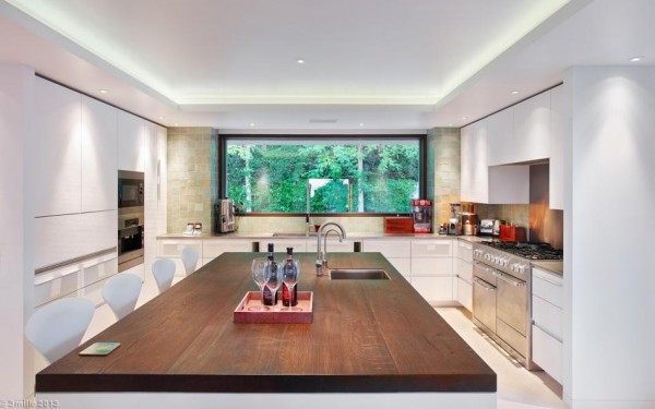 In the kitchen, a large central island is an extra prep space as well as a casual dining or observing bench for four.