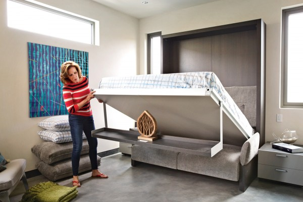 An ingenious drop down bed, which incorporates a wall display shelf, transforms a sofa space into a guest sleep space with ease.