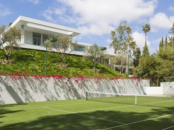 A long exterior staircase meanders down the side of the grassy hillside, leading to a full-sized astro-turf tennis court with floodlights.