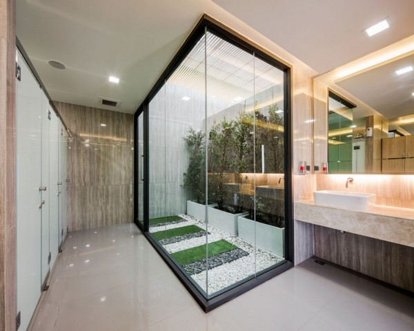 A neat, simply zen internal courtyard brings the green outdoors into a screened-off, windowless bathroom area. The indoor garden provides an unexpected feature on approach, and a pleasant view when emerging from the private stalls.