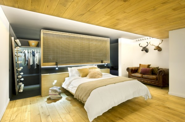 A natural oak and sewer grate headboard forms a floating wall, behind which a walk-through closet can be accessed.