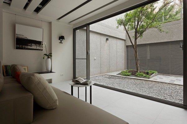 Our first modern Asian home looks out onto a courtyard that features a complimenting minimalist design, encased in pale walls that similar to the those of the adjacent interior.