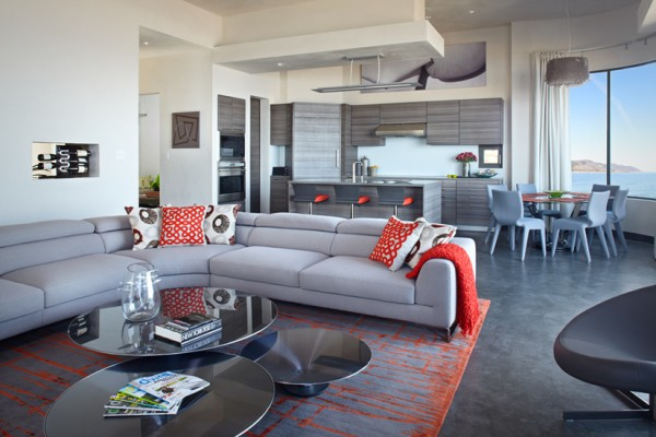 Hot orange accents bring vibrancy to a neutral gray and white backdrop in the open plan living area that features a lounge, kitchen and dining area.