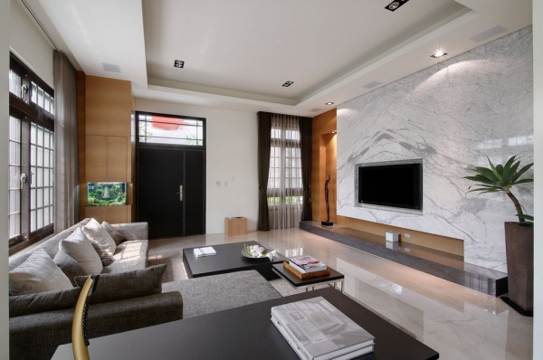 A long hearth decorates the foot of the feature wall, which has a soft lighting arrangement that illuminates a letterbox recess where ordinarily a fireplace might be situated. The adjacent alcove too is illuminated, drawing attention to the warm wood cladding and featured sculpture art.