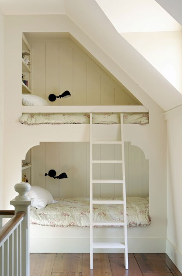 Bunks under a sloping roof, like in this loft space, are a great solution where precious floor space is eaten by a central stairwell. This particular example also incorporates a set of space saving storage shelves in each bunk cubby.