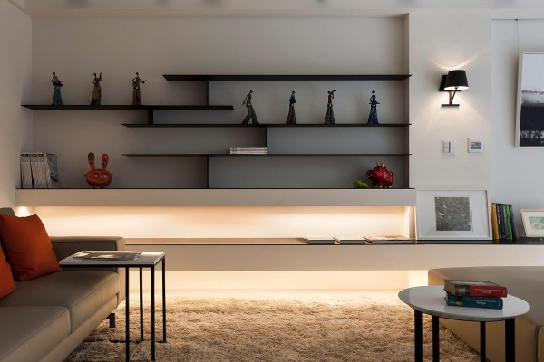 Low level lighting creates a cozy glow along the length of the room, in absence of a fireplace. Simple black shelving, in a distinctly oriental style, provides plenty of room for display pieces–though the collection is well spaced to prevent the area from appearing at all cluttered.