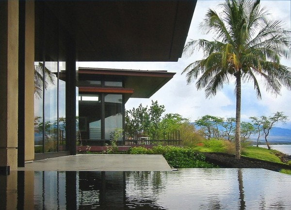 Large retractable glass doors disappear to allow the modern home to open up to the private infinity pool, beautifully lush landscaped gardens, and sparkling ocean view to the horizon. The slide-away walls also facilitate natural gentle cooling of the home, utilizing the refreshing sea breeze.