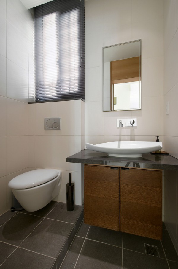 In the bathroom, The toilet cistern has been concealed in a small false wall to give a streamlined look, and the furniture is all suspended off the floor. These uncluttered options are great for smaller bathroom designs, as more visible wall and floor space tricks the eye into believing the area is larger than its actual modest dimensions.