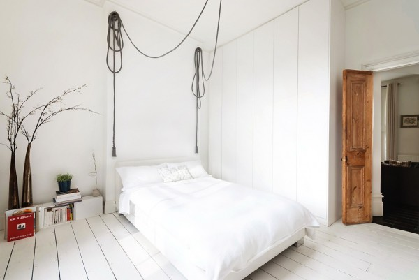 The bedroom takes on an industrial feel with free hanging bulbs on reams of cable. The walls are kept free from clutter.