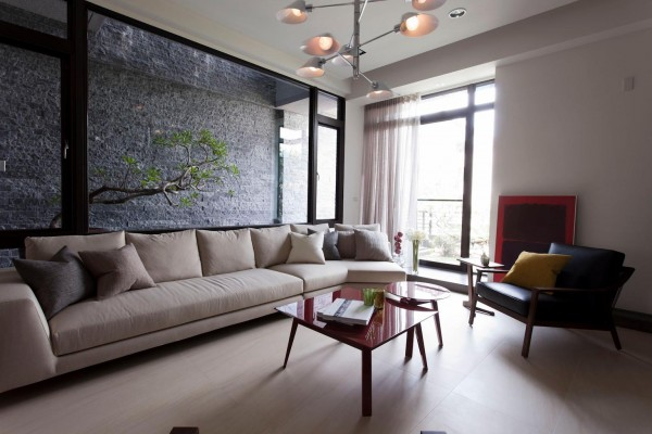 In our second home design, a slate courtyard wall becomes a feature wall to this living room, and is a brilliant backdrop for some bright red accent furniture and artwork.