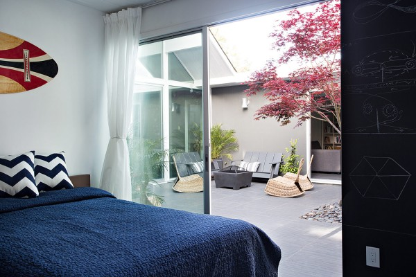 A modern bedroom scheme, complete with blackboard feature wall, spills out onto the courtyard too.