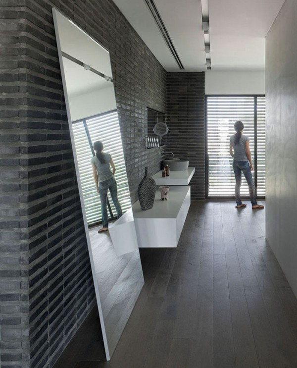 The master bedroom has a luxurious en suite bathroom, fitted with floating vanity units and a modern freestanding bath tub. The crisp white furniture sings against the same slate gray brickwork as is seen in the spacious living area.