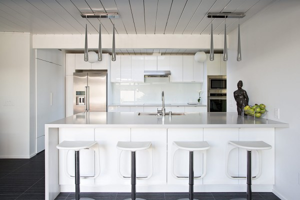 A huge kitchen island acts as a breakfast bar for casual dining, as well as playing home to the kitchen sink. Low hanging task lighting defines the area.