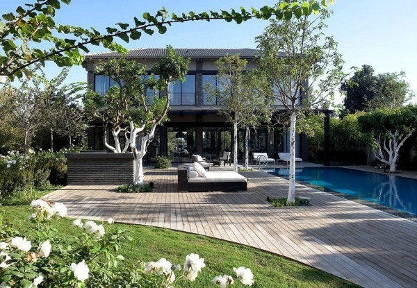 In contrast, the pool decking sweeps away in a curvaceous manner, making way for a lush lawn and planting.