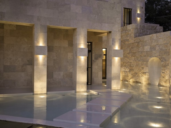 The entranceway is decorated with more Travertine stone and a pretty reflecting pool.