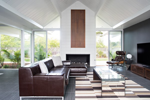 Rich autumnal browns decorate the lounge area, bringing warmth to the white surrounds. The garden can be seen beyond the glazed wall, which brings in a swathe of luscious green.