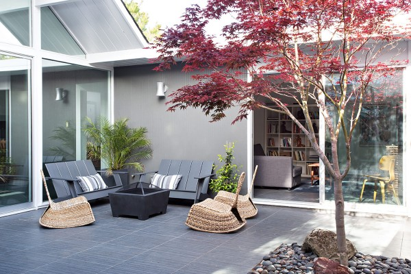 The same gray flooring runs inside and out, making the courtyard feel like just another sociable room of the home.