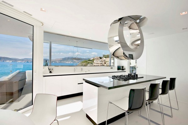 A highly contemporary chrome extractor design is the star of the show in this slick ice-white kitchen with sharp black trims. The central cooking island also doubles a casual eating area for four diners.