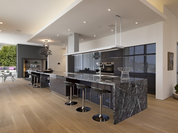 A huge kitchen is kitted out with Gray lacquer DADA units and a dramatic stretch of granite countertop.