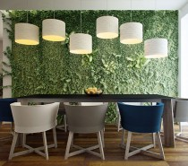 Nothing says '21st century' quite like a green wall. Bringing some of the outdoors inside while taking up minimal floor space and improving indoor air quality, a green wall adds loads of colour and texture to a design. If you plan to install one, look for a space like this near large windows, because living plants require ample light indoors. Also, plan from the beginning how your plants will get their water, and where the excess water will go. These pendant lamps express the design elements of rhythm and repetition, while adding surprise with varied heights. They almost look like musical notes on paper!