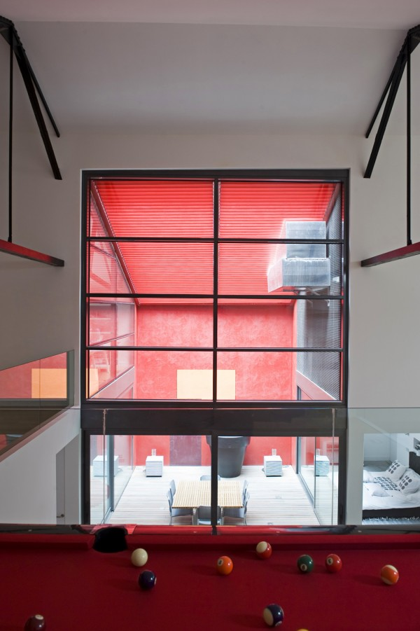 Above, a recreational area with a pool table overlooks the courtyard. Blinds overhead match the courtyard wall adding a punch of colour to all the interior spaces overlooking the courtyard.