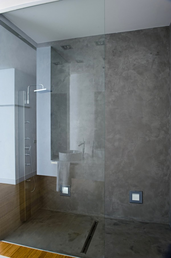 Industrial concrete is refined by a smooth buffed finish, footlights, and a linear drain, along with the latest shower technology, including rain head and a handheld unit.