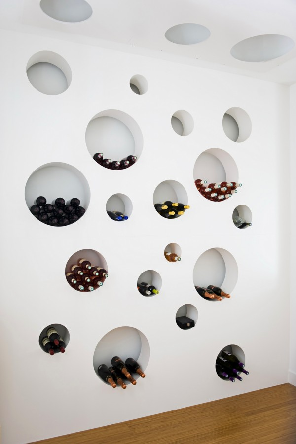 The wine cellar's circular shelves are perfect for accomodating bottles and groups of bottles in varying sizes. The motif continues onto the ceiling where  the circles become recessed lights.
