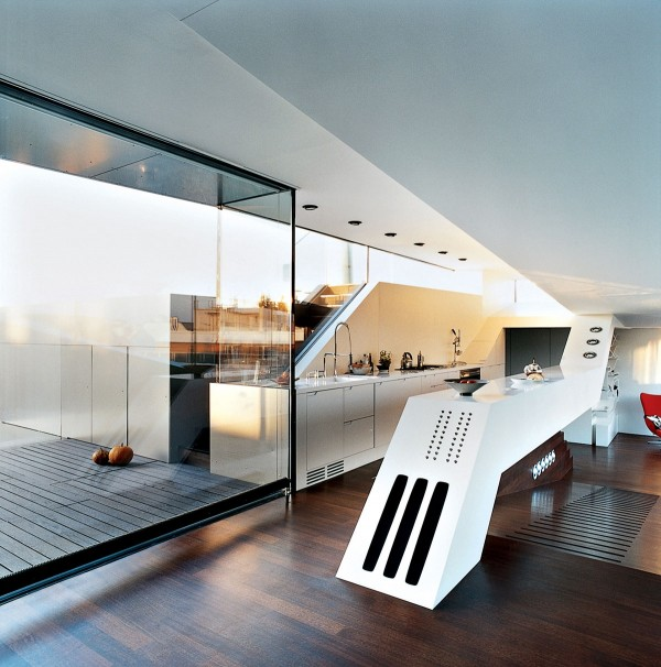 The awesomely unique angular counter is definitely a centerpiece in this narrow penthouse kitchen.