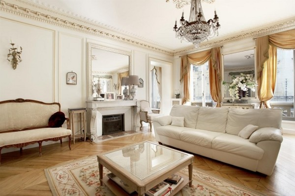 This Parisian home clearly embraces its roots with gorgeous crown molding, delicate chandeliers and beautiful antique furnishings. Still, we can see hints of the more modern in the white leather sofa and worn coffee table.