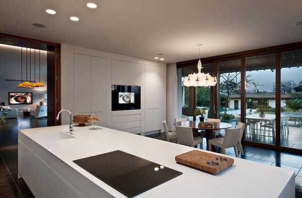 The modern kitchen is so sleek it barely seems a part of the same house, but the light fixture over the kitchen table hints at the overall theme.