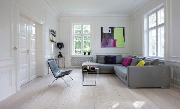 Tying the colors of the throw pillows into the artwork creates even more fun contrast in this white and grey room.