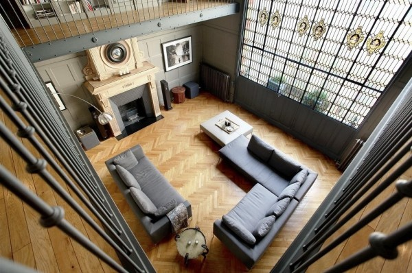 Simple sofas and subtle lighting turn this almost medieval space into something perfect for a modern Parisian bachelor.