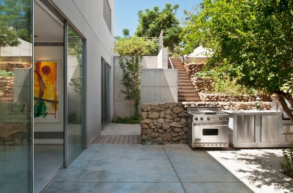 And an outdoor entertaining area is kept simple but cozy with irregular rock walls and greenery.
