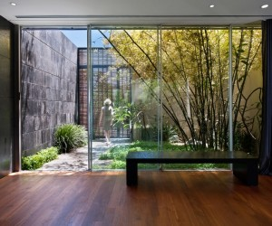The front entrance makes use of the same sliding window panes, making it difficult to distinguish nature from home.