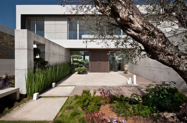 The home's entry is carefully landscaped with mosses and colorful, native plants.