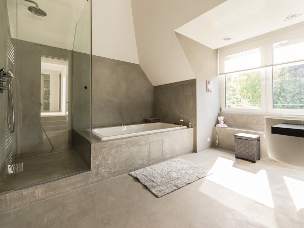 Sleek bathrooms in white tile and gray slate stay true to the home's modern designs while still providing a relaxing atmosphere for the home's occupants.